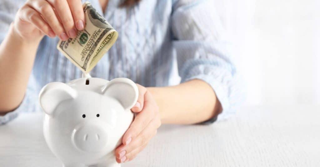 Woman saving money into piggy bank